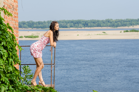 Young brunette girl is standing on the balcony of the old against the backdrop of the river and looking thoughtfully into the distance