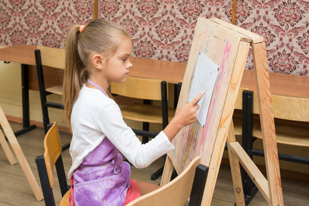 additional training: Girl artist paints on an easel to draw circle