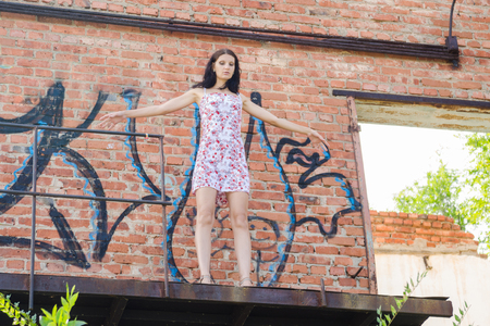 Woman with arms opened standing at the edge of a building ledge Foto de archivo