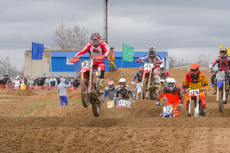 off road racing: Volgograd, Russia - April 19, 2015: Motorcycle racer after the start of driving on the road by a large group, at the stage of the Open Championship Motorcycle Cross Country Cup Volgograd Region Governor