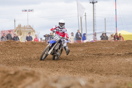 cross leg: Volgograd, Russia - April 19, 2015: Motorcycle racer insured against falling outstretched leg in the corner, at the stage of the Open Championship Motorcycle Cross Country Cup Volgograd Region Governor Editorial