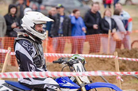 start to cross: Volgograd, Russia - April 19, 2015: Motorcycle racer smiles before the start of the competition, at the stage of the Open Championship Motorcycle Cross Country Cup Volgograd Region Governor
