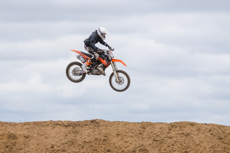 motorcycling: Volgograd, Russia - April 19, 2015: Motorcycle racer jumped above the ground on the springboard, at a stage of the open championship motorcycling Cup cross-country Volgograd Region Governor