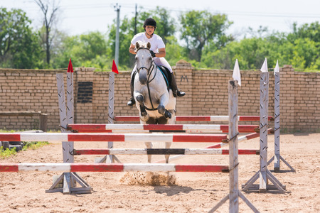 horse show: Volgograd, Russia - June 19, 2016: The sportswoman on a horse show jumping phase passes with multiple barriers
