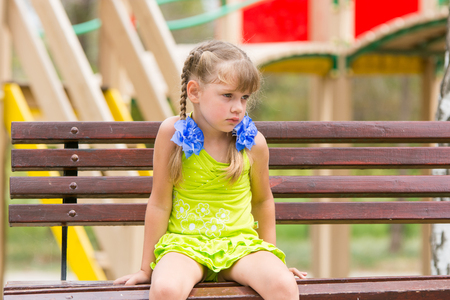 Offended five year old girl sitting on a bench and crying