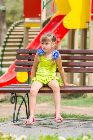 wants: Upset girl sitting on the bench on the background of the playground Stock Photo