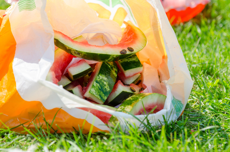 neatly stacked: Watermelon rind with seeds lie in a plastic bag on the green grass
