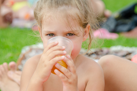 The girl drinks juice from a plastic disposable cup on a picnic