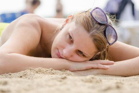 Sad young girl lying on sandy beach and looking to the side Stock Photo