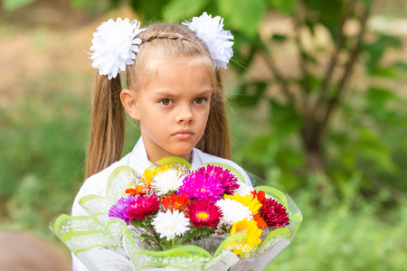 Portrait of a seven-year schoolgirl with a big bouquet in hands