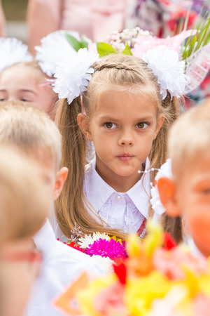 Thoughtful first grader in the crowd of classmates on line the first of September