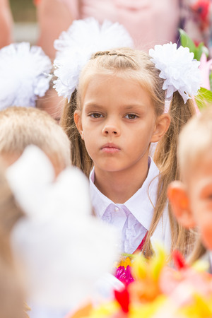 First grader tired of classmates in the crowd at the first line of September Stock Photo
