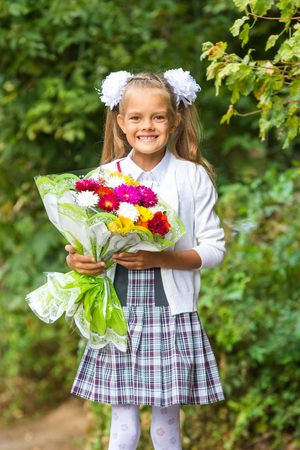 First grader with a bouquet of flowers smiling happily Stock Photo