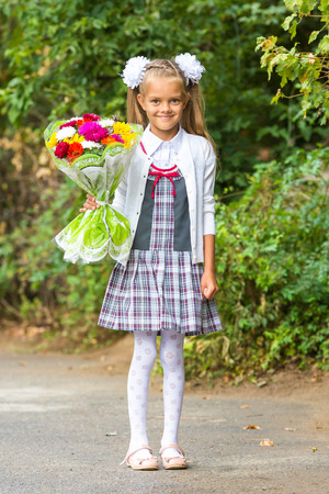 first year student: portrait of a seven-year first-grade girl with a bouquet of flowers
