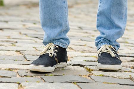 Pieds, habillé, dans, jean bleu, et, espadrilles homme, closeup, sur, trottoir pierre