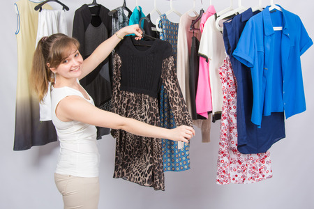 Happy girl chose a dress in the wardrobe Stock Photo