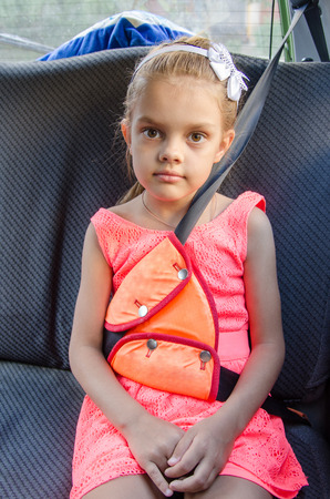 restraint device: A child of six sitting in the back seat of the car and strapped in using a restraint device