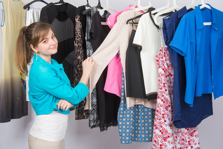 looked: Young girl chooses clothes in the wardrobe, and looked into the frame