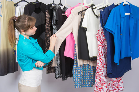 chooses: Young girl thoughtfully chooses clothes in a wardrobe Stock Photo