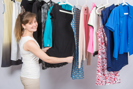 chooses: Girl chooses clothes and with a smile, looked into the frame