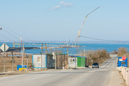 taman: Taman, Russia - November 5, 2016: Construction of a bridge across the Kerch Strait, the control checkpoint on the road leading to the building, at the shoreline of the Taman peninsula, as of November 2016 Editorial