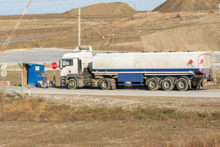 taman: Taman, Russia - November 5, 2016: Verification of documents from the driver tank truck at security checkpoint protected area