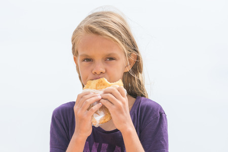looked: A hungry girl with an appetite chews delicious cake and looked into the frame Stock Photo