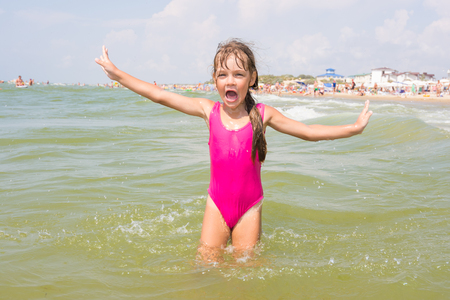 The girl in the pink bathing suit joyfully shouts and gestures by going into the water Stock Photo