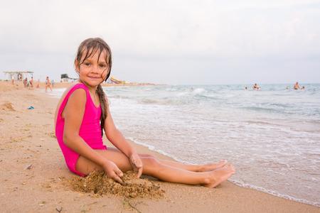 Five-year girl sitting on the beach seaside