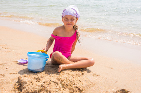 resort life: A child plays in the sand shovel and bucket on the sea shore