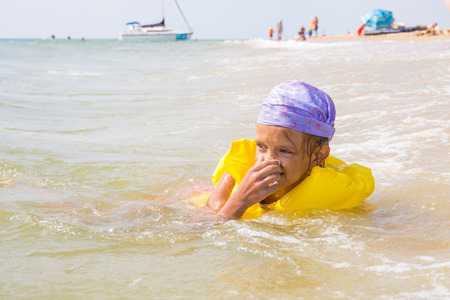 The girl choked and hit the water in the nose, while she was bathing in the sea Stock Photo