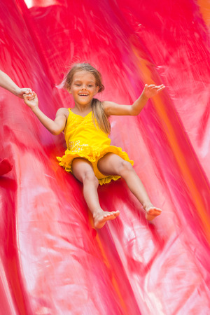 playground rides: Child drives off the high inflatable trampoline Stock Photo