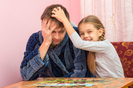 motility: Daughter fun soothes tired dad who collect puzzles Stock Photo