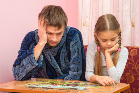 tortured: My daughter collects a picture from puzzles, tired dad sitting next