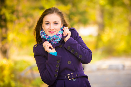 Girl in a dark blue coat against the background of autumn leaves