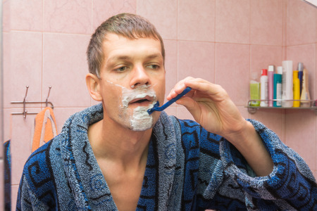 mirro: Young man shaving in front of mirro
