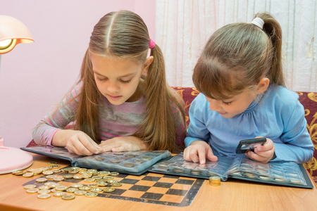 numismatist: Two children studying coins in album Stock Photo