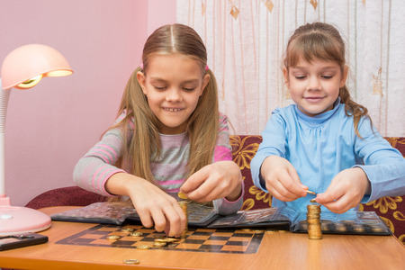 numismatist: Two children build towers of coins