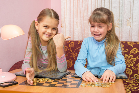 numismatist: Two girls at the table collected montki one cries, the other laughs at it Stock Photo