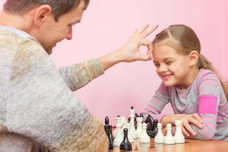 debate win: Dad won a game of chess at a daughter on a bet and hit her on the head Stock Photo