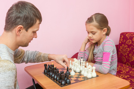 Dad teaches his daughter to make first moves in chess