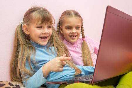 Two girls looking at a laptop and laughing merrily, one is pointing at the screen
