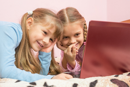 authenticity: Sisters watching a cartoon on a laptop and laughing at a funny moment