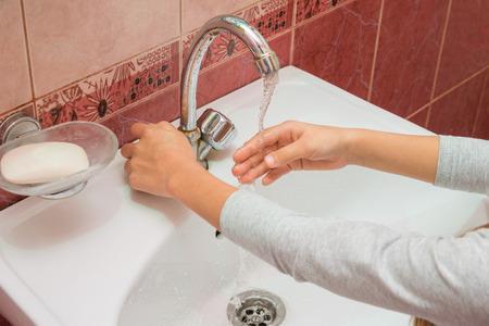 冷たい水の流れの下の手の子フレーム