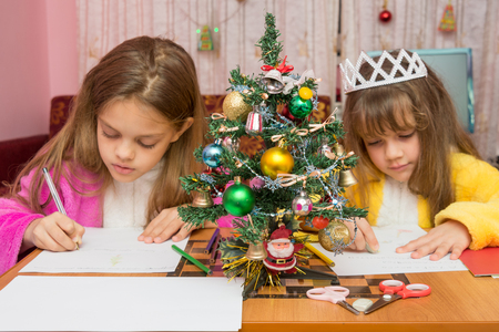 treasured: Two girls write a letter to Santa Claus, the focus is on the fur-tree in the middle Stock Photo
