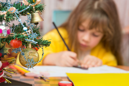 Carried away by a girl making Christmas crafts, focusing on the fur-tree Stock Photo