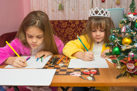 treasured: Two girls writing Christmas greeting letter sitting at the table at home Stock Photo