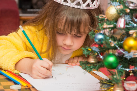 The girl draws a picture in a letter to Santa Claus