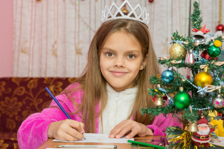 desires: A girl waiting for a new year, writes a letter to the desires and looked into the frame Stock Photo