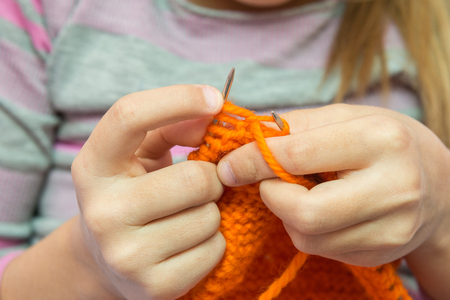 Close-up of children hands to knit with needles